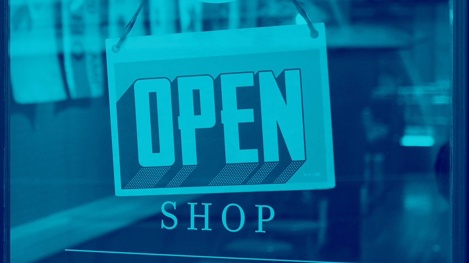 An 'open for business' sign in a shop window