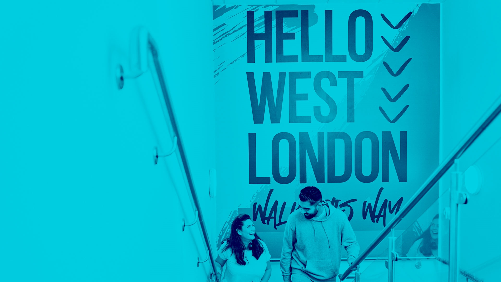 Staff walking up stairs with a 'Hello West London' backdrop